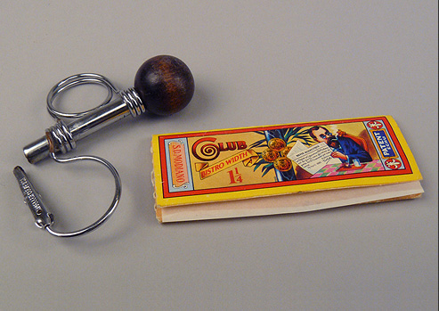 Metal roach clip and rolling paper for smoking marijuana.
