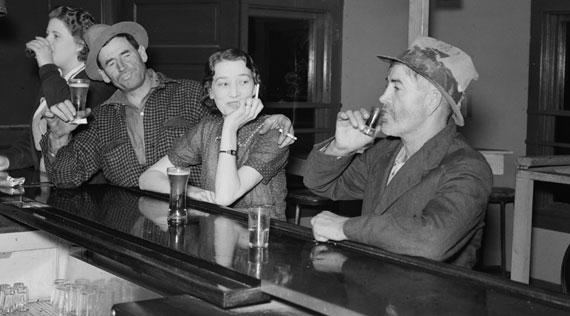 Black and white photograph of four people drinking alcohol at a bar.