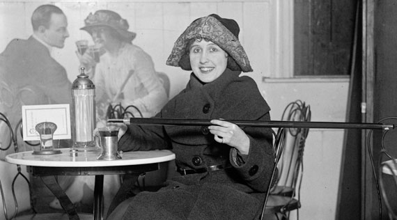 Woman sitting in café pouring alcohol into her glass from a hollowed out cane.