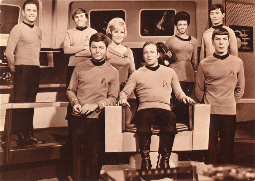 The cast of Star Trek in costume, 6 men and 2 women of various ethnic backgrounds.
