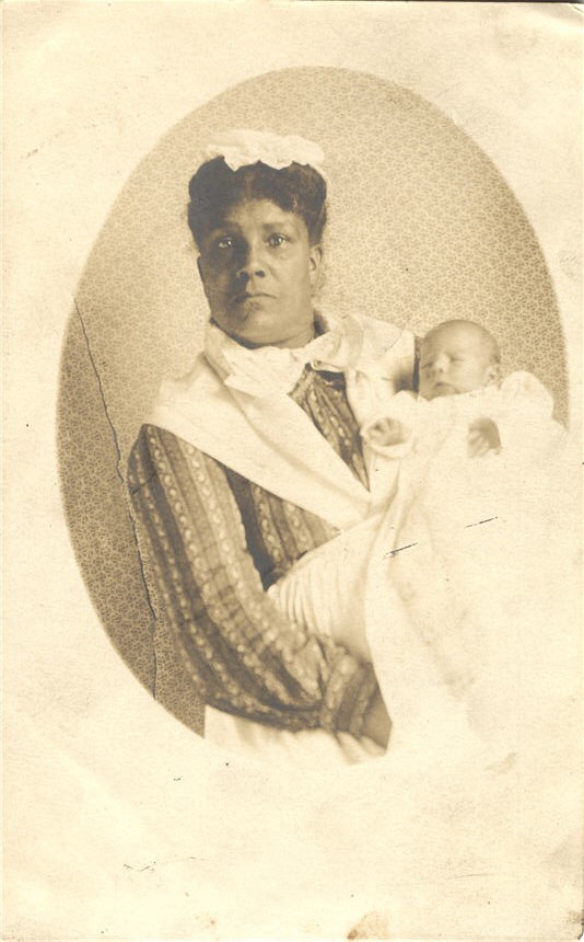 An African American female nurse in white holding a White infant, looking at the viewer.