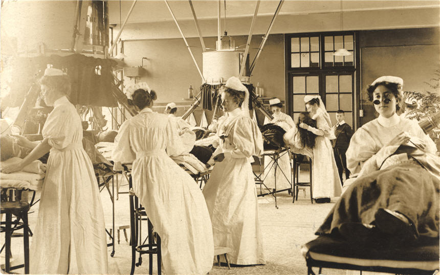 Groups of White female nurses, some wearing goggles, administer treatment to patients.