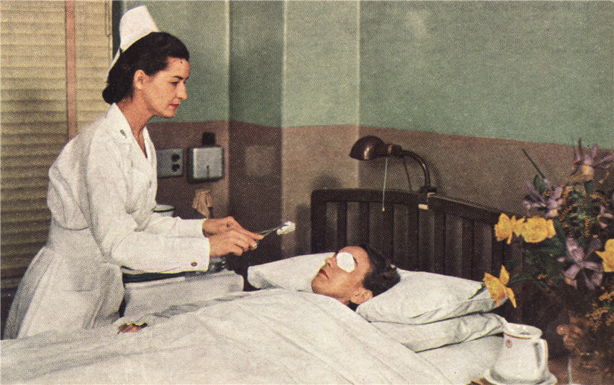 White female nurse treating a White female eye patient, lying in bed.