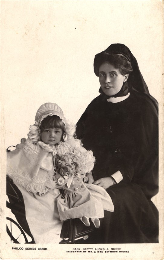 A white female nurse in black sitting next to a White girl in a small carriage with a doll.
