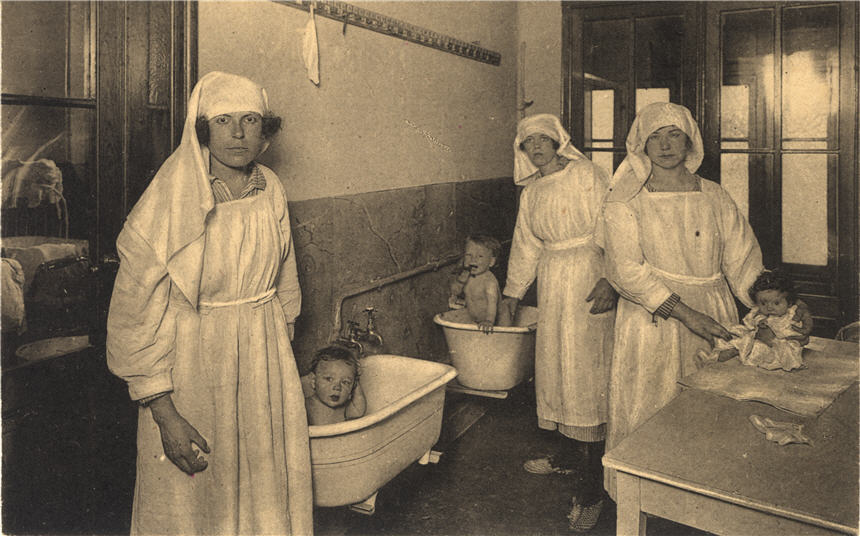 Three White female nurses tend to three White babies, two of which are in tubs.