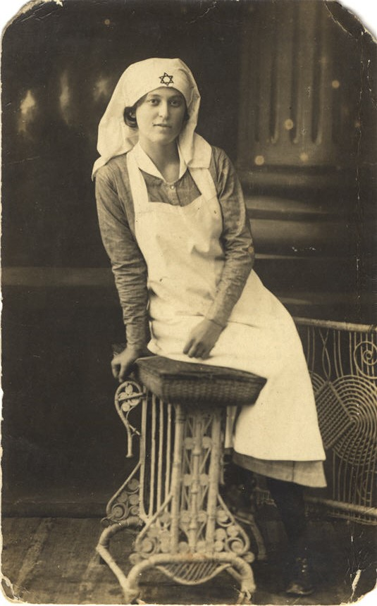 A White female nurse in white apron, leans on a cushion and looks at the viewer.
