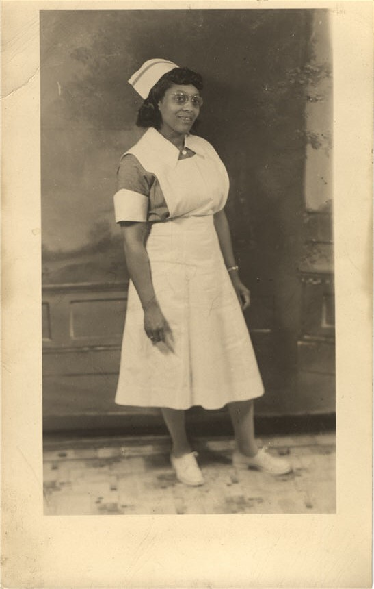 An African American nurse in white stands and looks off to the right.