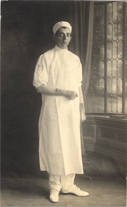A White male nurse in white, stands in a studio and looks at the viewer.