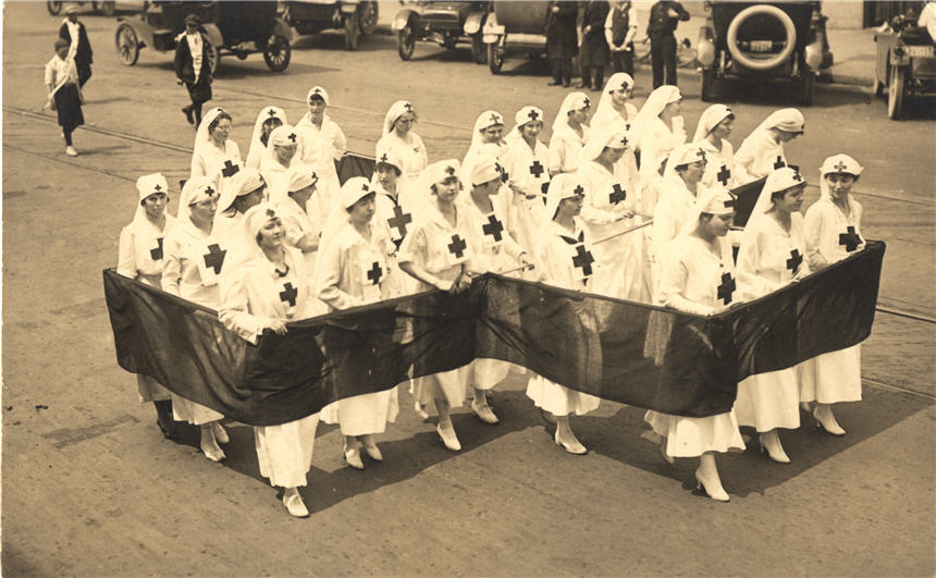 A group of White female Red Cross nurses in white march in a cross formation.