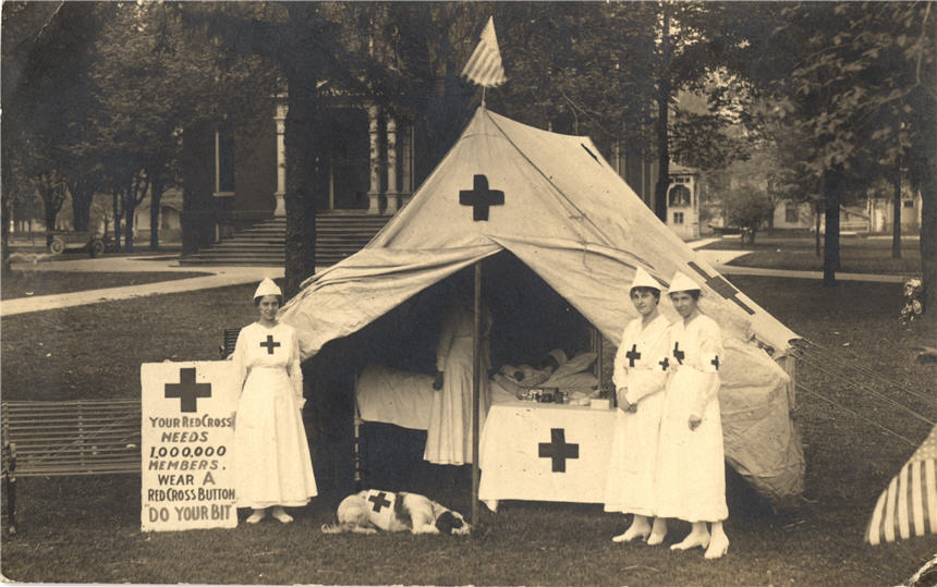 Three White female nurses stand outside a tent, as another woman tends to a man inside the tent.