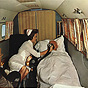 A White female nurse in white holds oxygen up to an elderly White male patient in an airplane.