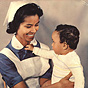 A Surinamese nurse in blue and white smiles at a Surinamese baby on her lap.