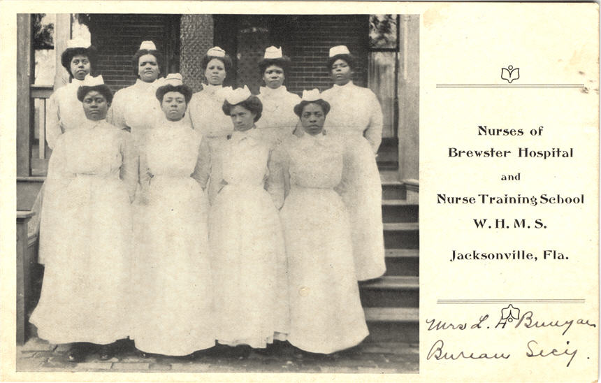 Nine African American female nurses in white standing in a group looking at the viewer