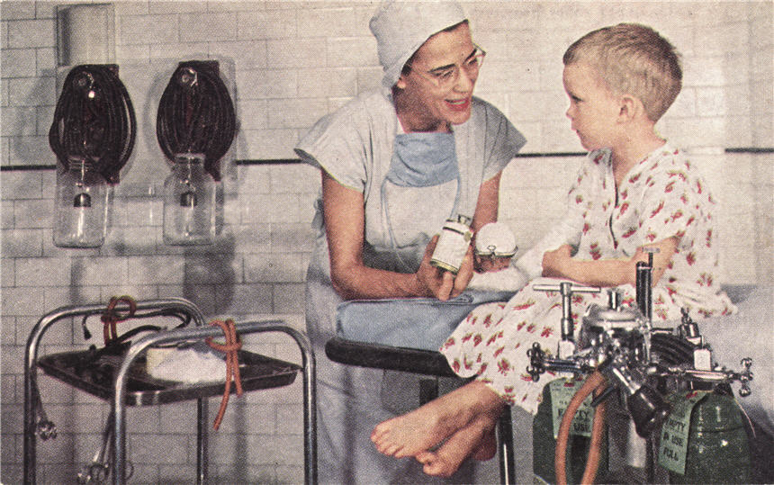 A White female nurse anesthetist talking to a White boy sitting on an operating table.