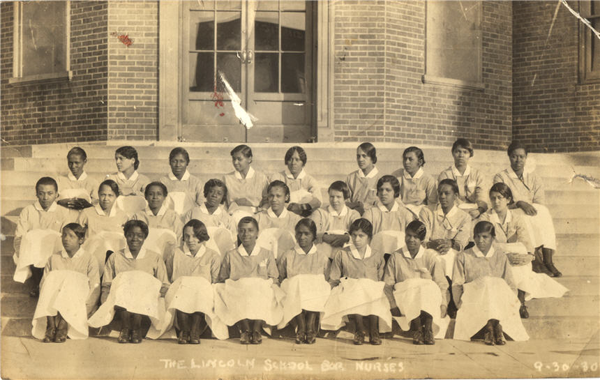Twenty-six African American female nursing students sitting on steps.