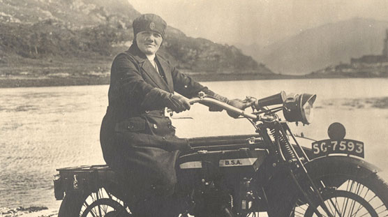 A White female nurse on a motorcycle, looking at the viewer, castle in background.
