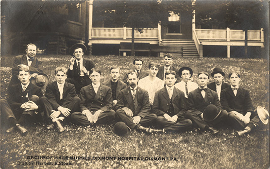 Fifteen White male nurses sitting in a group on a grass lawn.