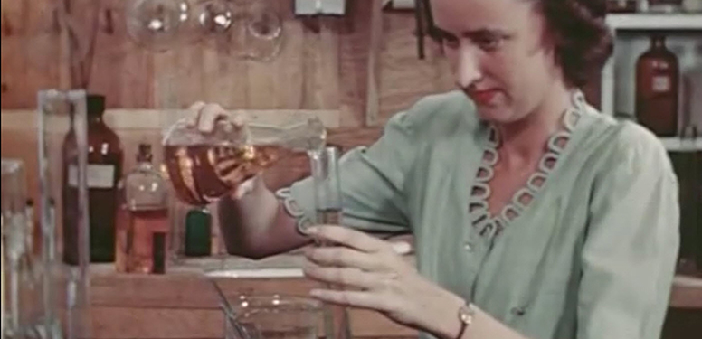 A white woman pours a yellow liquid into a tube