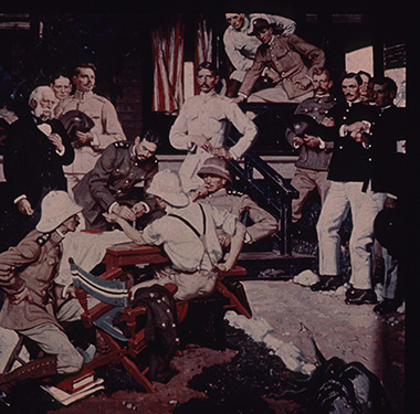 A white man receives an inoculation in a roomful of military personnel