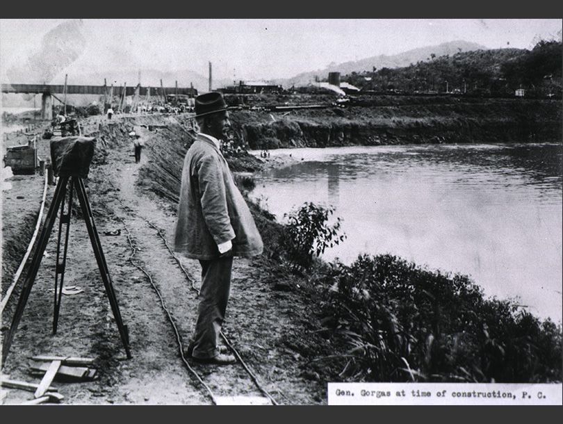 A photograph of a white man looking at a body of water at a construction site