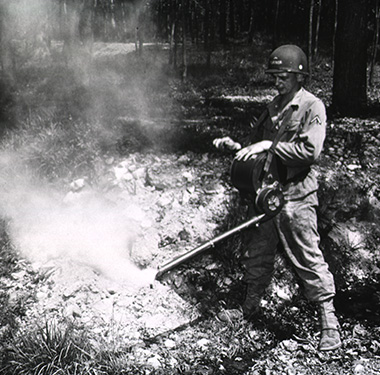 A photo of a white soldier in the woods spraying mist from an apparatus