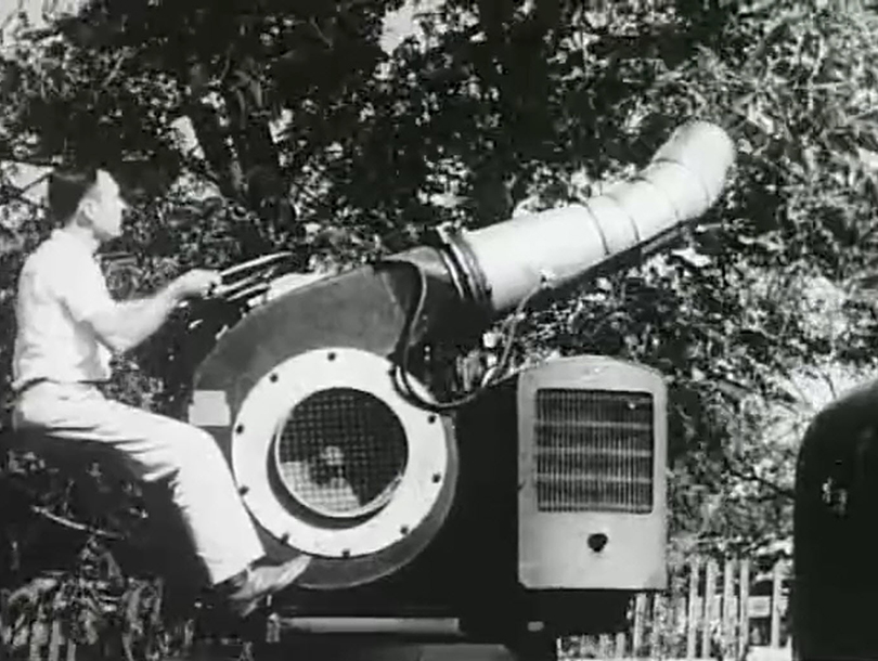 A white man uses a large apparatus to spray pesticide on trees