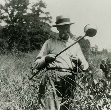 A photo of a white man surrounded by tall grass with a large scoop in hand
