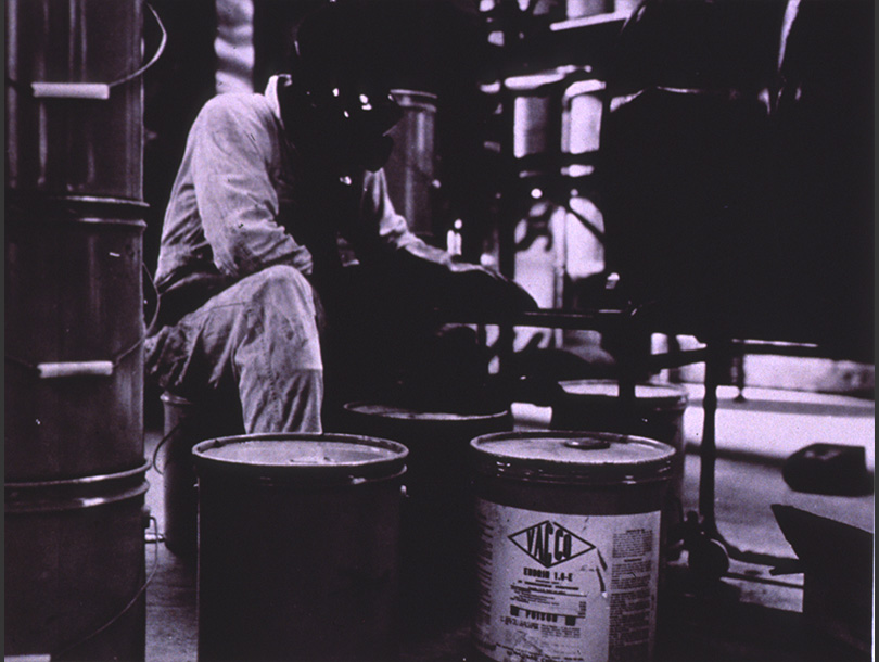 A man sits on drums of pesticide