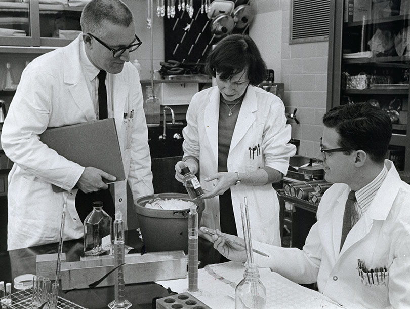 A picture of one woman and three men in a lab