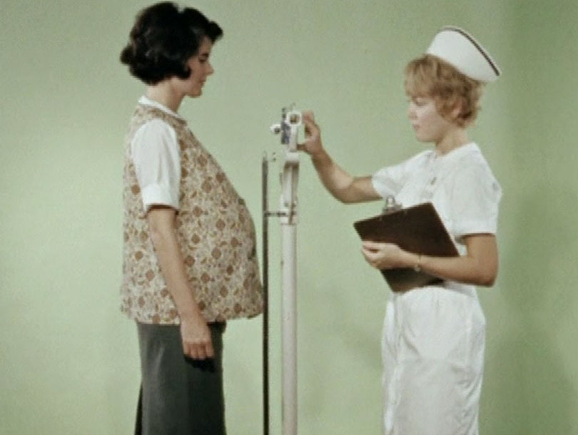 A pregnant white woman is weighed by a white female nurse
