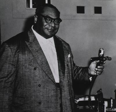 Three quarters, right pose of King Tauf-Ahau Tupou III of Tonga demonstrates a jet injector for smallpox immunization.