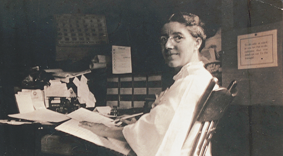 A woman at seated at a desk, turning towards her left to look at viewer.
