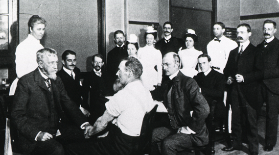 Dr. Mitchell examining a male patient in left foreground while a group of men and women look on.