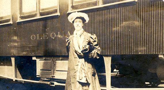 A woman in dress and hat standing in front of a train car.