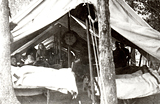 Historical photograph of a tent in the woods