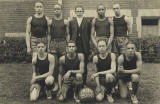 Charles Drew with the rest of the Dunbar High basketball team-- four are kneeling in a front row with a basketball on the ground, and five stands on the back row where Drew is on the left. ca. 1921