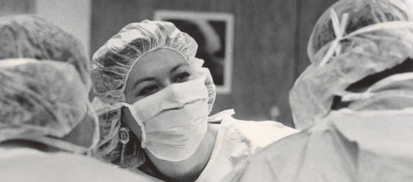 A woman and two other people in surgical garments