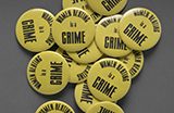 Several yellow metal buttons that read 'Women beating is a crime.'