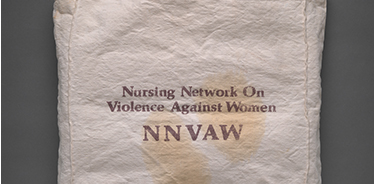 White cloth bag with handle and writing that says 'National Network  On Violence Against Women NNVAW'.