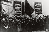 Large crowd of White men and women hold banners on a street facing the viewer.