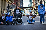 Six White people sit and stand in a street holding hands, one person is in a wheelchair.