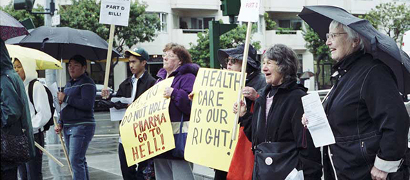 A logo plus a multiracial group of protesters in rain, holding signs, protesters in foreground are elderly.