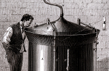 A man stands next to a large cylindrical beer vat and gazes into the vat through a small opening in the conical cover