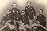 Five Civil-War era amputees in military uniform gathered together for a photograph