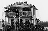 Historical photograph of men gathered outside a house