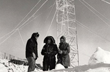 Three people wearing parkas in a snowy environment, with a radio tower in the background
