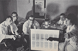 Four seated White men in lab coats look on as a White woman points towards a back lit board