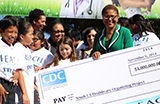 African American woman holds a large check, surrounded by a multiracial group of people