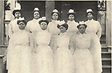 Nine African American female nurses in white standing in a group looking at the viewer.