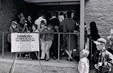 Photograph of people standing in line outside a clinic